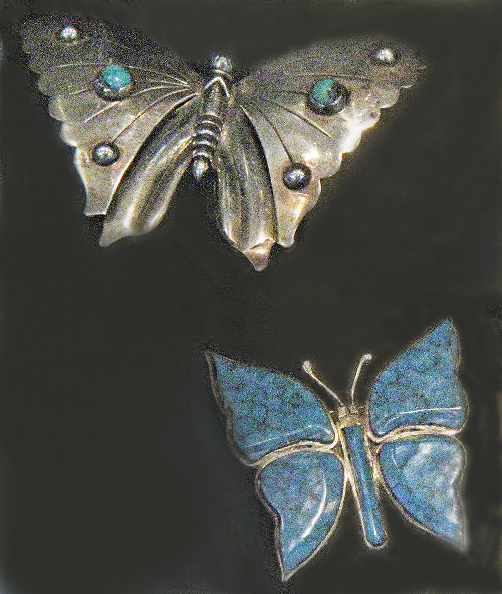 Additional butterfly pins, of later date, from Jonathan Hill booth. Silver one is set with turquoise and silver bosses, while other has bezel-set wings of turquoise.
