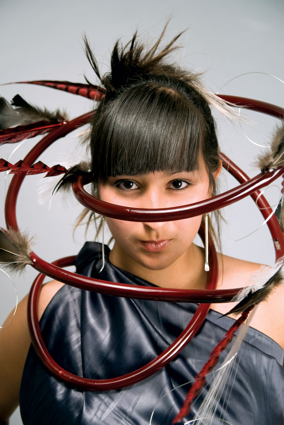 POSTMODERN BOA of stainless steel, sterling silver, enamel paint, and feathers, by David and Wayne Nez Gaussoin (Picuris Pueblo/Diné), 2009.  Model: Tazbah Gaussoin. Photograph by David Gaussoin; courtesy of Museum of Indian Arts and Culture.