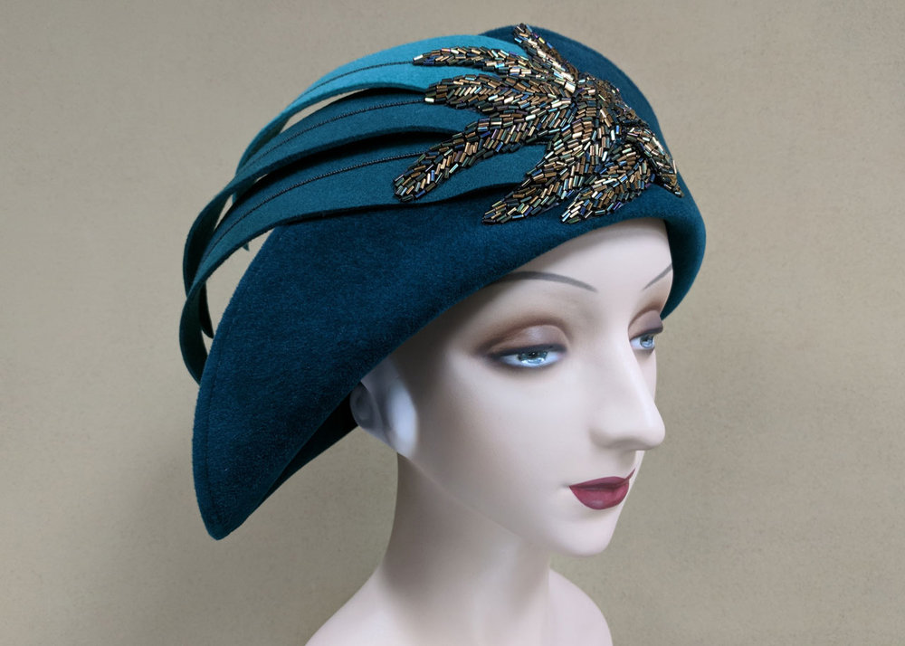 FEATHER TOQUE of teal velour felt, hand-cut and wired felt feathers, bronze and iridescent green beaded appliqués, 2016.