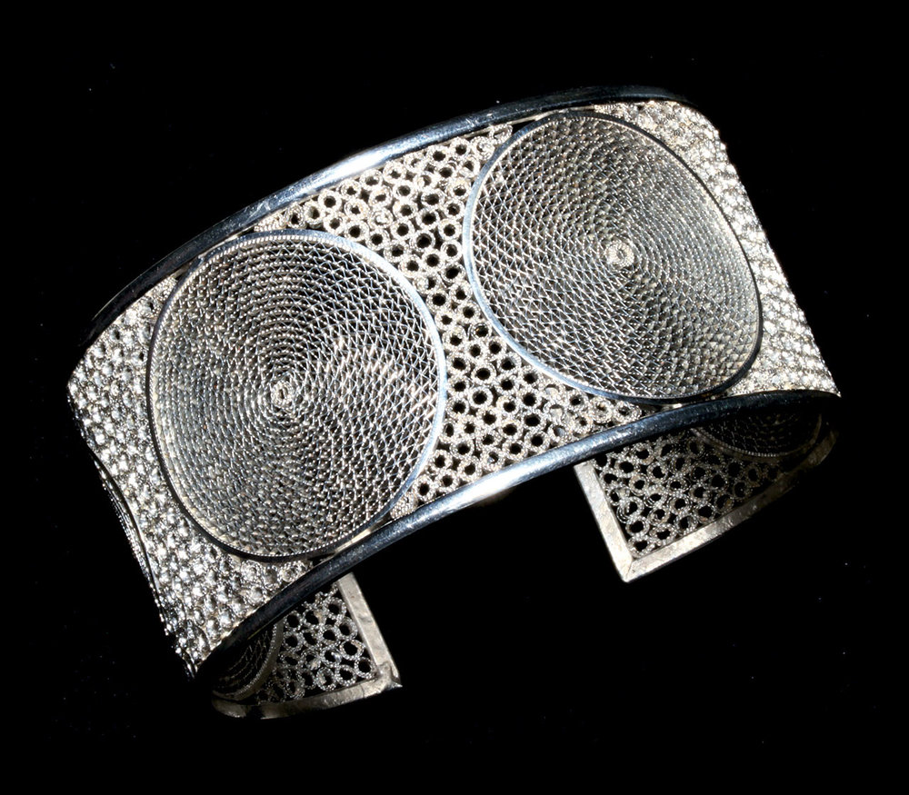 SILVER FILIGREE BRACELET by Jorge Moscoso. Moscoso's work is exceedingly fine openwork filigree. A mixture of silver and copper is used for the finely powdered solder, with borax as the flux. Then the torch flame is carefully applied, taking into consideration the finer and larger components to be heated and soldered. The work is produced among colleagues in his workshop.