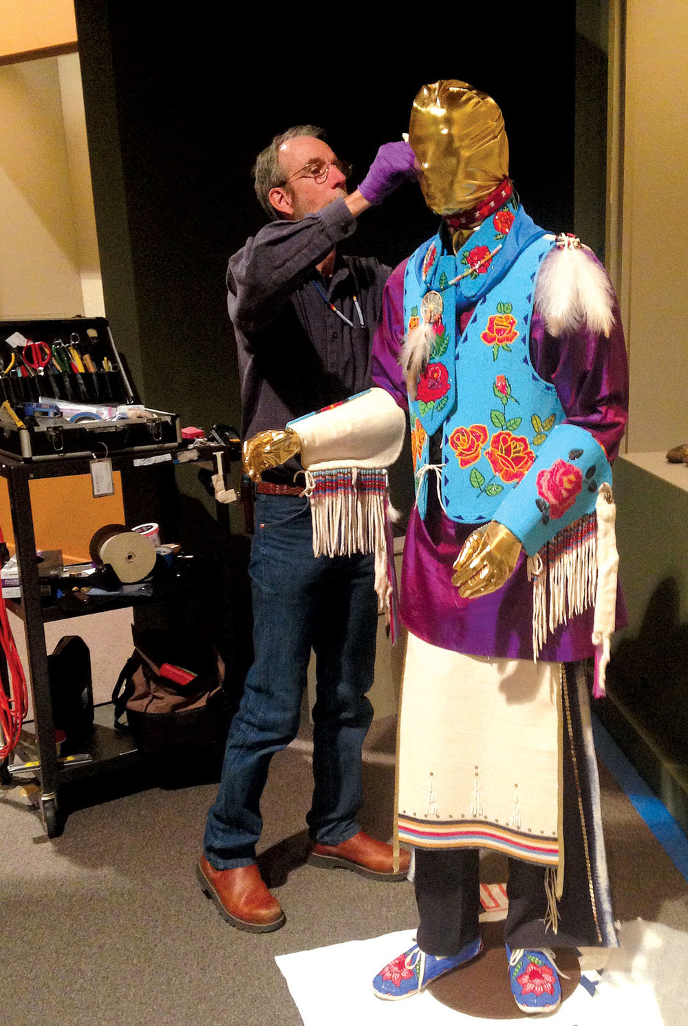 "JACK TOWNES dresses a commercial mannequin, the ""Kennequin,"" in Ken Williams's regalia.  Photograph by Cheri Falkenstien-Doyle."