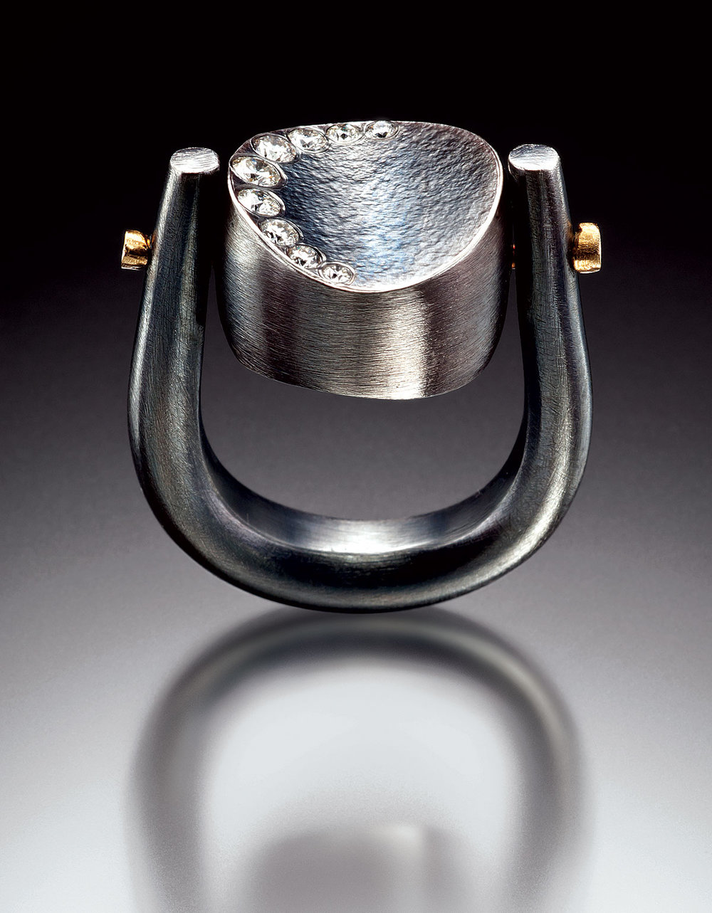 "FLIP RING of oxidized sterling, eighteen karat yellow gold, white diamonds, 3.2 x 1.9 x 1.6 centimeters, 2011. ""The band on this piece was hand-forged, and the center bead was hollow form construction with stars flush set on one side and a diamond crescent moon set on the other side."""