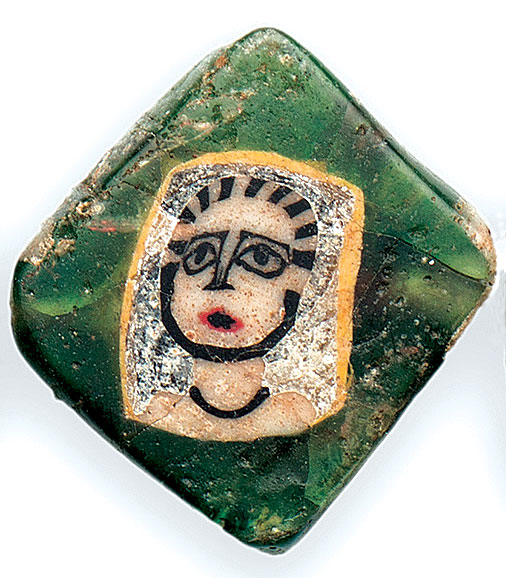 ANCIENT NUBIAN FACE BEADS:  LOZENGE-SHAPED TABULAR ROMAN MOSAIC FACE BEAD from Nubia. The rhomboid cane of Gorgon as a woman lacks any overlaid hair, and has a simple black bar as a necklace, like the face cane from the Crimea. The surrounding glass is badly cracked and appears whitish; it is approximately 1.2 x 1.5 cm.