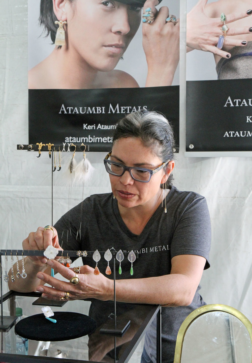 KERI ATAUMBI adjusting the display of several earrings at her booth. Ataumbi is a jeweler who blends the contemporary and traditional in her work, with pieces that range from the opulent to the minimalistic. She was recently the cover feature of Ornament Volume 40.1.   www.ornamentmagazine.org/shop/ornament-print-edition-volume-401