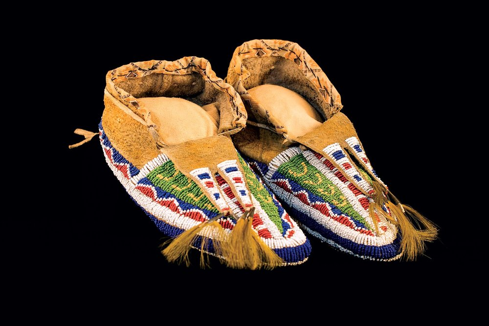 MOCCASINS WITH BEADED SOLES (Sioux) of cowhide, glass beads, sinew, tin tinklers, cow tail hair, prior to 1890. Commonly thought to be for use in burials, moccasins with beaded soles were in actuality a way to honor living people. They were used in ceremonies, to recognize individual achievement and to show status. Some have wear on the soles, confirming that they were worn to walk on.