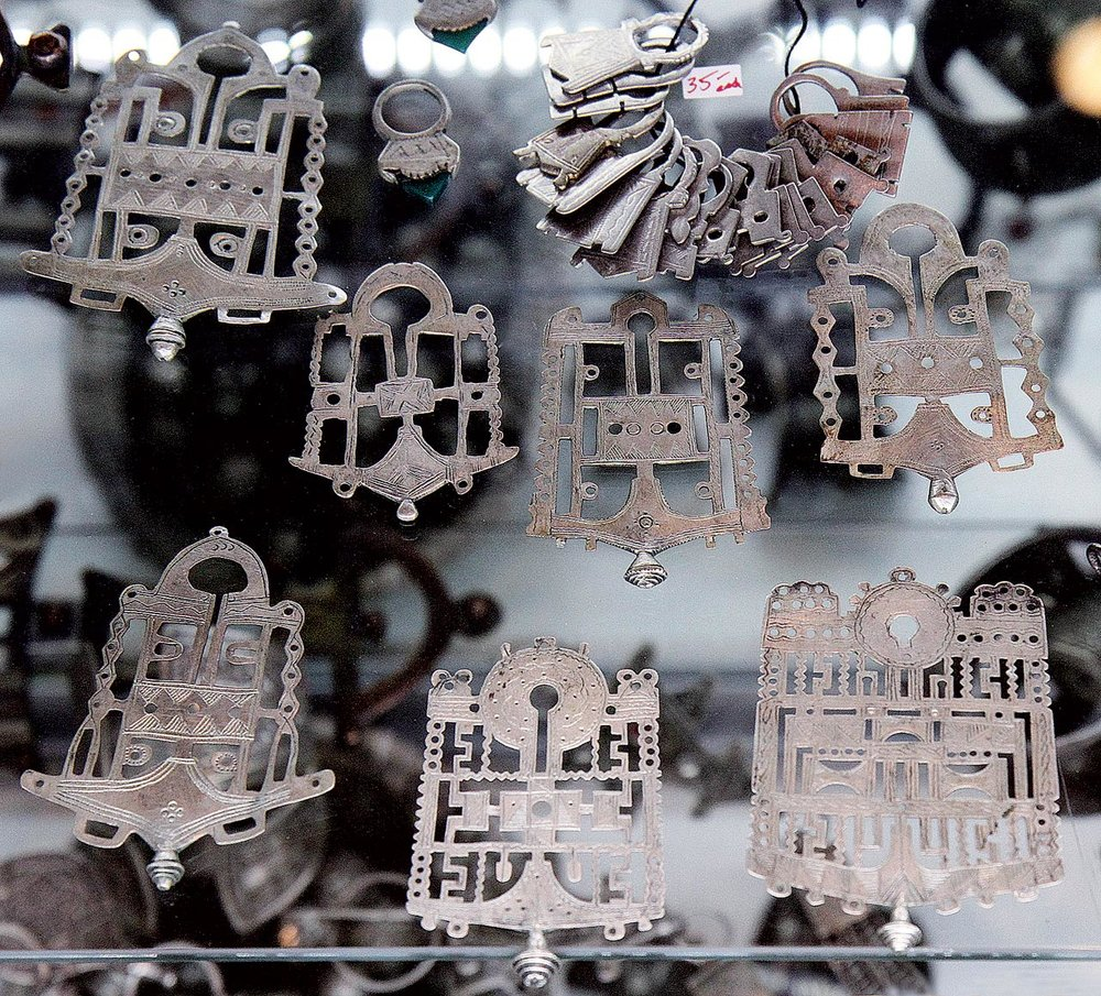 OLD SILVER PENDANTS. Niger, open-work/pierced pieces, these were normally sewn onto the front of a leather  kitab  or amulet, holding verses for the Qur'an and/or other protective writings, and worn as a necklace. Small  tisek  rings at top middle with agate or carnelian made in Idar-Oberstein: these were woven into women's hair as ornaments: old, Niger, also Mali. Small silver and metal hair ornaments on a string are mostly from Niger. Many of these are a stylized form seen in North African jewelry of the Punic goddess Tanit, with a triangular shape topped by a circle, sometimes with a horizontal line where the circle and triangle meet, like arms.  Courtesy of Ethnic Embellishments.