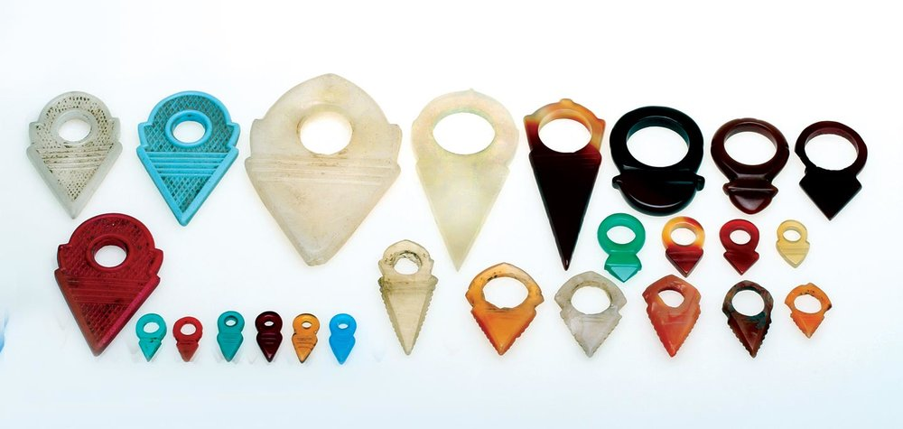 AGATE AND MOLDED GLASS TALHAKIMT,  TALHATANA  AND  TURMRINGS . 1.7 - 7.5 cm long: the oldest are the Indian made agate/carnelian talhakimt (the tall triangular type in pale agate) and talhatana (short triangular type) on the bottom right-hand row, from an ex-museum collection. While these reached West Africa via Mecca (Fisher 1984), and have been discussed by Gabus (1982) and Liu (1977) as to their being the prototypes of European copies in stone and glass, they have never been found in a Tuareg jewelry context, nor the much later German celluloid example, second from right top row or the German agate turmring type (1960s) next to it. Most used are the large agate talhakimt (white pre-1960, red 1960s) and the shorter talhatana types, also on right-hand side of top row. See Kaspers (2018 this issue on dating such agate ornaments) on the Idar-Oberstein industry that made these ornaments. German and English terminology for these ornaments differ (Kaspers 2018, Liu 1977). The smaller talhatana, in either heat-treated or dyed forms are usually worn in the hair, but not by Tuareg, as are the small, molded Czech/Bohemian glass ones. Large Idar talhakimt are also worn by the Dogon, and the larger glass ones in Malian necklaces.  Courtesy of the late J. L. Malter, R. Okrent, P.W. Schienerl; Abrima, the Picards, T. Stricker, L. Wataghani, and the Heimat Museum, Idar-Oberstein.