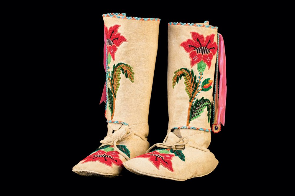 STEPPING OUT:  WOMAN'S MOCCASINS (Shoshone Bannock) of brain tanned elk hide, rawhide, glass beads, brass buttons, sinew, cotton thread, commercial ribbon, 1920–1940. The floral patterns on these Great Basin moccasins were inspired by designs on European and European-styled goods. The Shoshone became famous for their beautifully executed beaded flowers, especially roses.