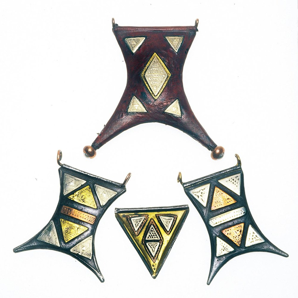 TUAREG JEWELRY:  THREE GERBA AND ONE TRIANGULAR TCHEROT AMULETS. Largest gerba-shaped one is new, of copper covered with leather, with cutouts revealing the white metal/brass panels, poorly engraved, with copper tube and large copper/white metal balls at the tips of the stylized goatskin form, 9.5 cm high and smallest 4.4 cm high. Lower ones are antique, of steel, silver, copper, and/or brass.