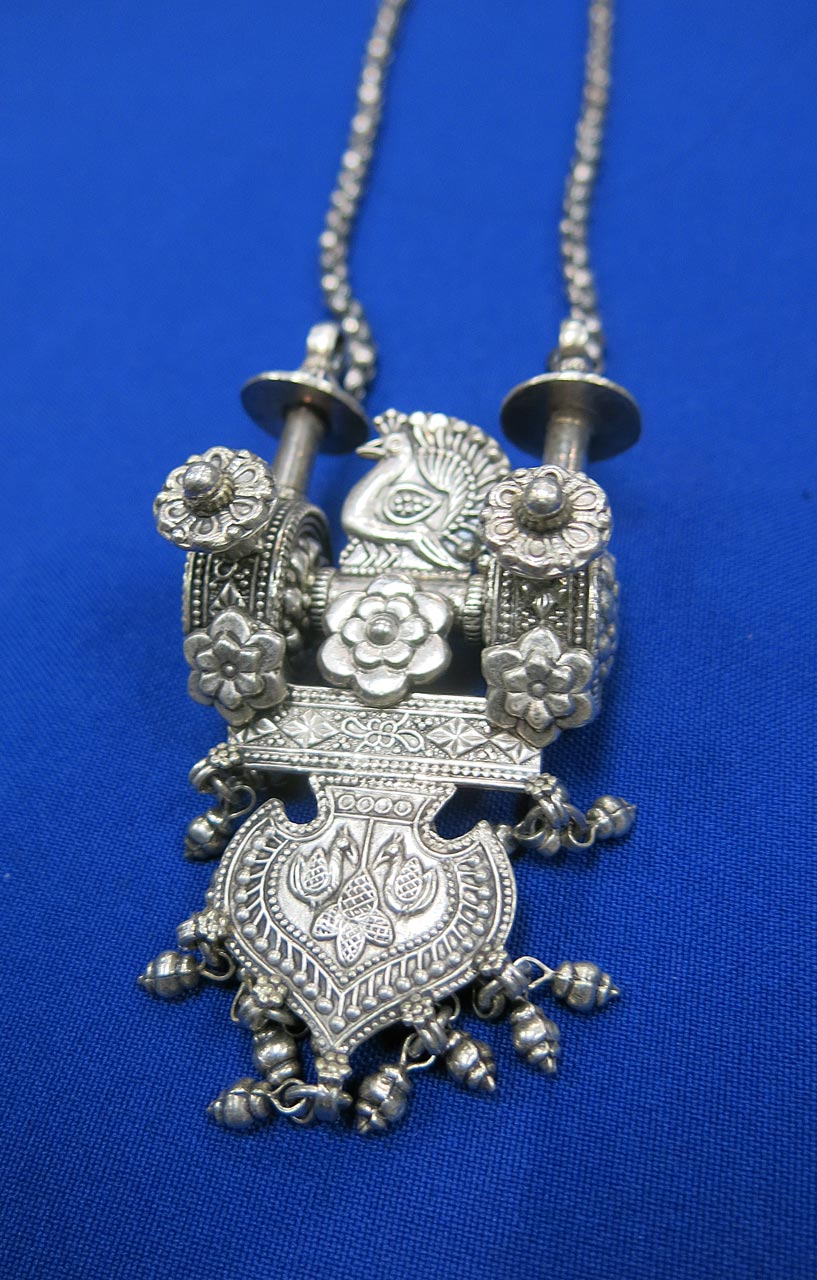 Silver pendant featuring peacock and flower designs.