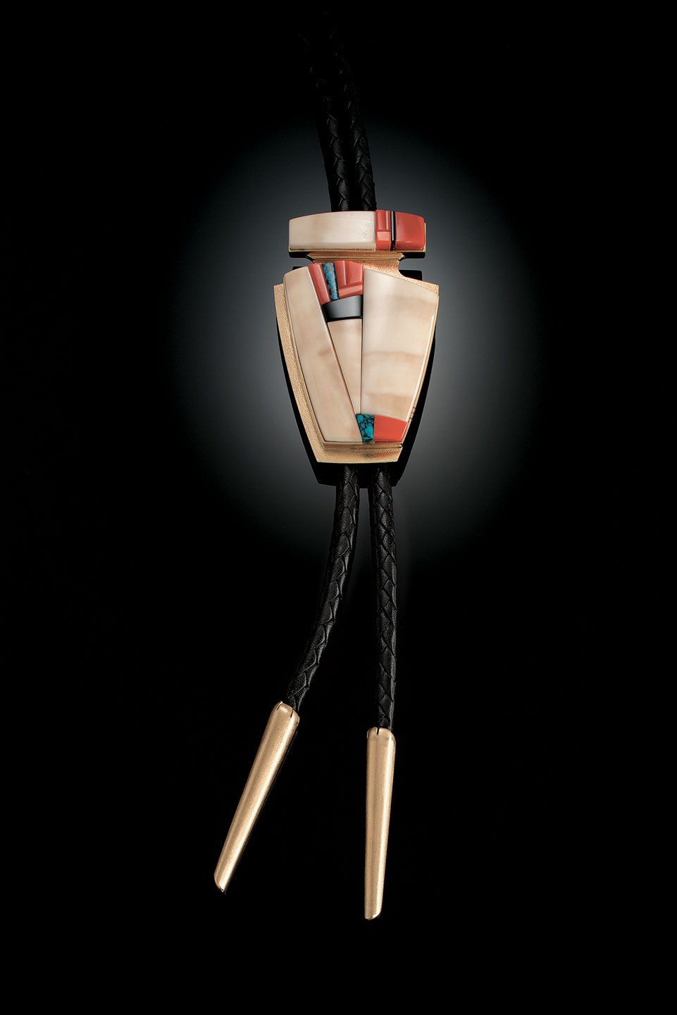 BOLO TIE of fossilized ivory, coral, black jade, turquoise, and fourteen karat gold, 8.3 x 5.4 centimeters, 1998.  Private Collection.