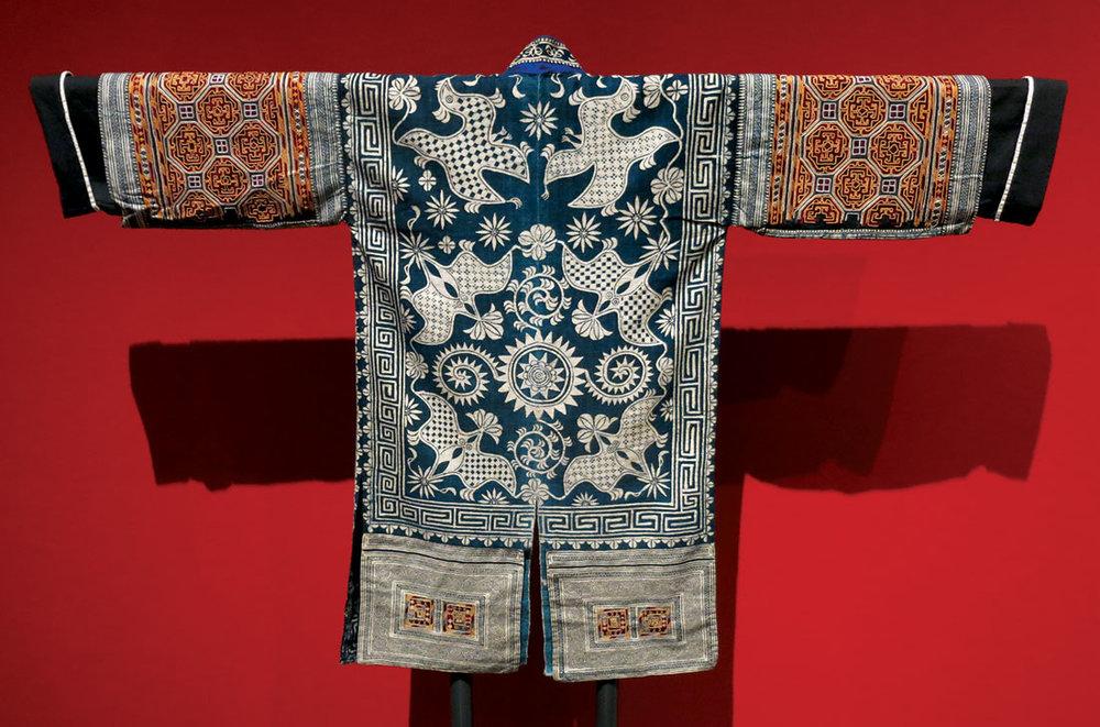 VANISHING TRADITIONS:  GEJIA WOMAN'S FESTIVAL JACKET (back) of silk, cotton, embroidered, indigo-dyed, Matang Village, Kaili City, Guizhou Province, China, mid-twentieth century.  Installation photograph of back of jacket by Patrick R. Benesh-Liu.