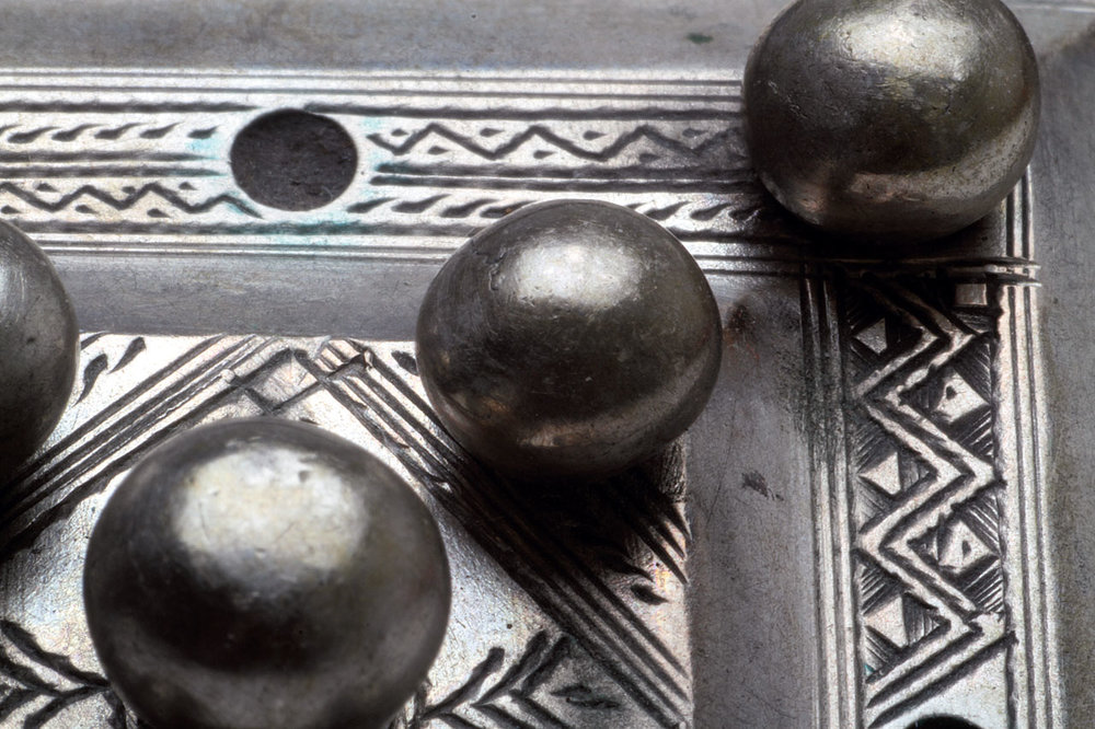 CLOSEUP PHOTOGRAPHY:  CLOSEUP MAURITANIAN/TUAREG PENDANT, showing the very precise engraving, done before the silver balls were attached. Note the jeweler's strokes, as well as slight errors in certain areas of the pendant. In the right margin, in a width of 1.8 millimeters, the jeweler has engraved seven lines. The uppermost silver ball is 0.6 cm in diameter.