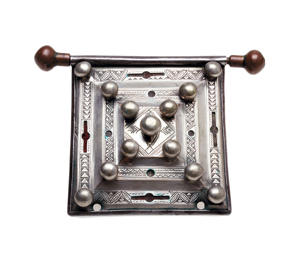 CLOSEUP PHOTOGRAPHY:  BEAUTIFUL MAURITANIAN OR TUAREG AMULET, of silver, copper with steel back; it has cutouts that once held red and most likely green-colored material, now too faded to determine their original color. The silver balls are decorative, as the stepped front is held onto the steel back by bezels, not rivets. Note the fine engraving. The pendant/amulet is 5.7 centimeters wide, not including the hanger.