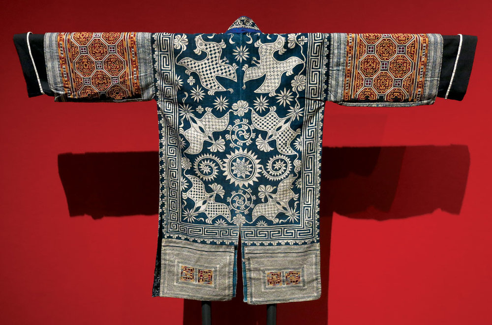 GEJIA WOMAN'S FESTIVAL JACKET, front and back, of silk, cotton, embroidered, indigo-dyed, Matang Village, Kaili City, Guizhou Province, China, mid-twentieth century.  Photograph courtesy of The Textile Museum. Installation photograph of back of jacket by Patrick R. Benesh-Liu.
