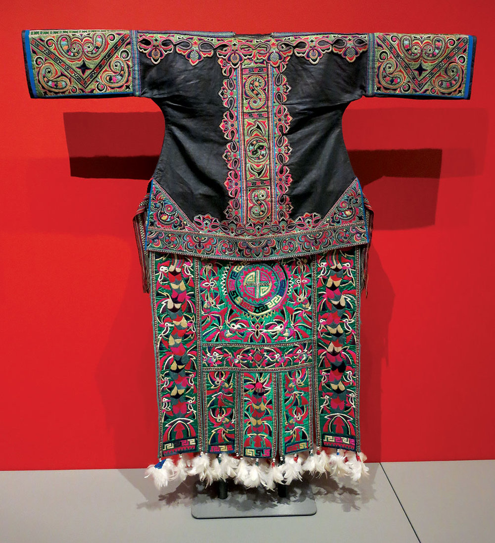 MIAO WOMAN'S JACKET of cotton, silk, embroidered, Yahui Township, Danzhai County, Guizhou Province, China, twentieth century. MIAO WOMAN'S APRON of cotton, silk, Job's tears, chicken feathers, embroidered, Rongjiang County, Guizhou Province, China, mid-twentieth century.  Photograph by Patrick R. Benesh-Liu.