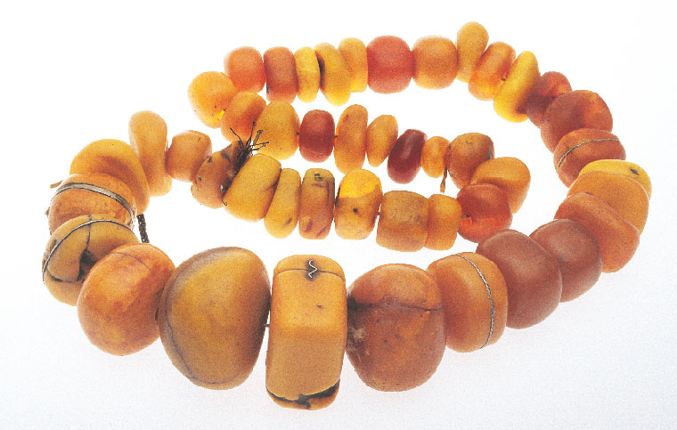 Superb strand of copal and amber from Morocco, maximum size of beads 5.8 cm wide; note repair to beads by binding with metal wire or bands, or with corrugated staples. Courtesy of Wind River. RKL