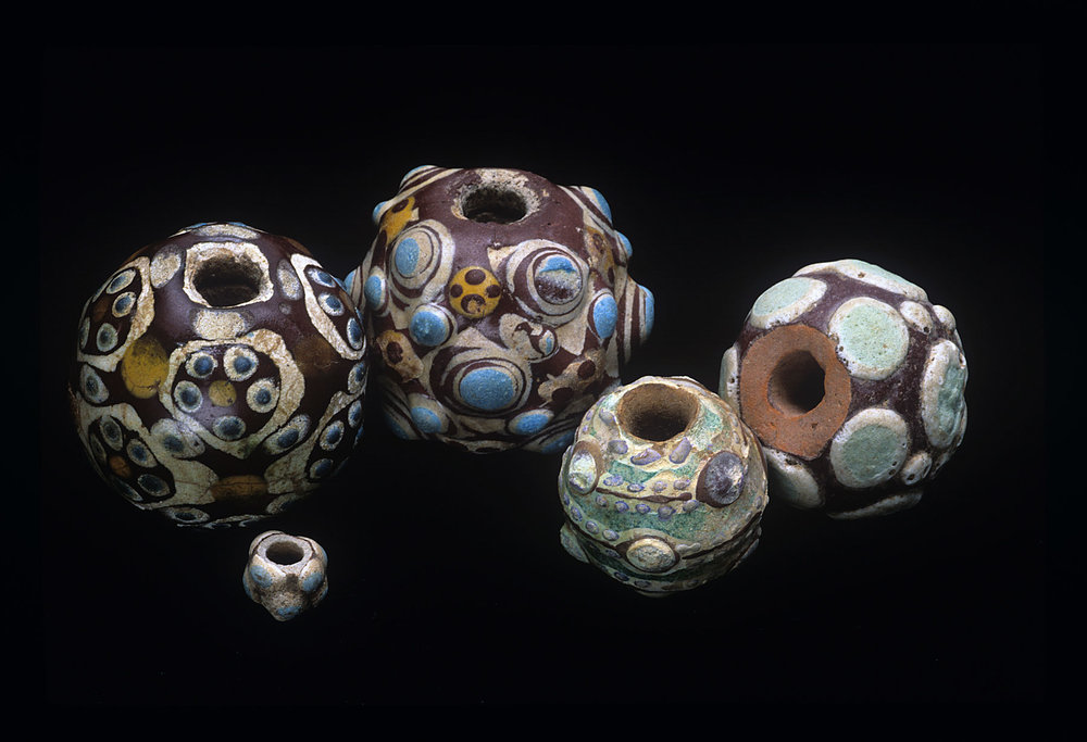 An array of Zhou Dynasty composite beads, decorated with simple and stratified eyes, as well as rosettes; note white or reddish cores, and glaze decorations. These range from approximately 0.5 to 2.0 cm diameters. For additional information, see Ornament 38/4, 2015 and 40/5, 2018. RKL