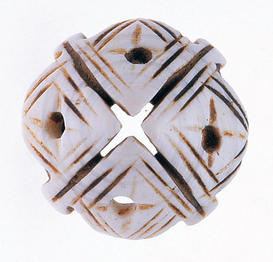 Conus shell whorl decorated by sawn lines and drilled holes; these are used as hair decorations in Mauritania and elsewhere in North Africa. These are also seen in metal transpositions. See Ornament 32/1, 2008 and 40/3, 2018. RKL