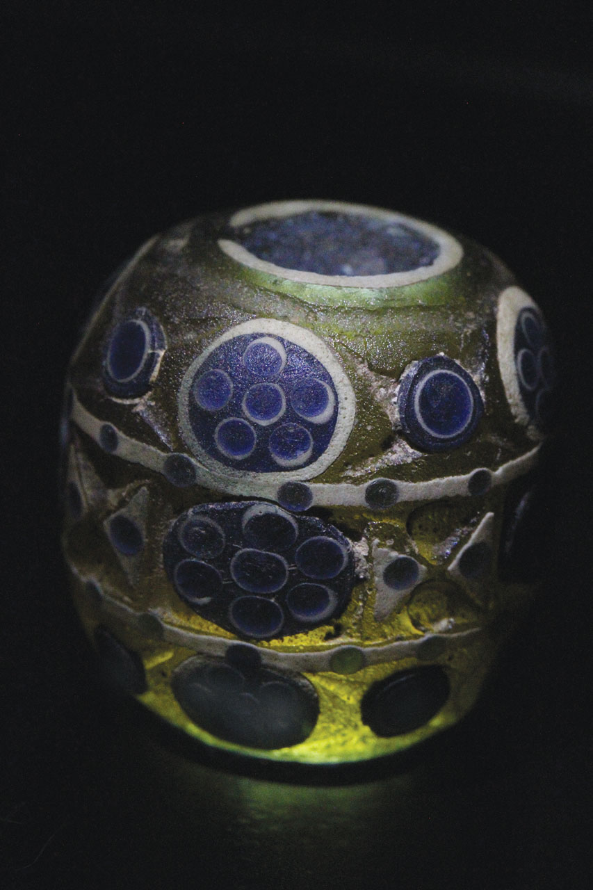 ZHOU SILICATE BEADS:  SPHERICAL BEAD WITH ROSETTES, EYES DIVIDED INTO THREE REGISTERS, on which dots have been pulled into crosses and triangles; note transparency of matrix.  Courtesy of SHMOG.
