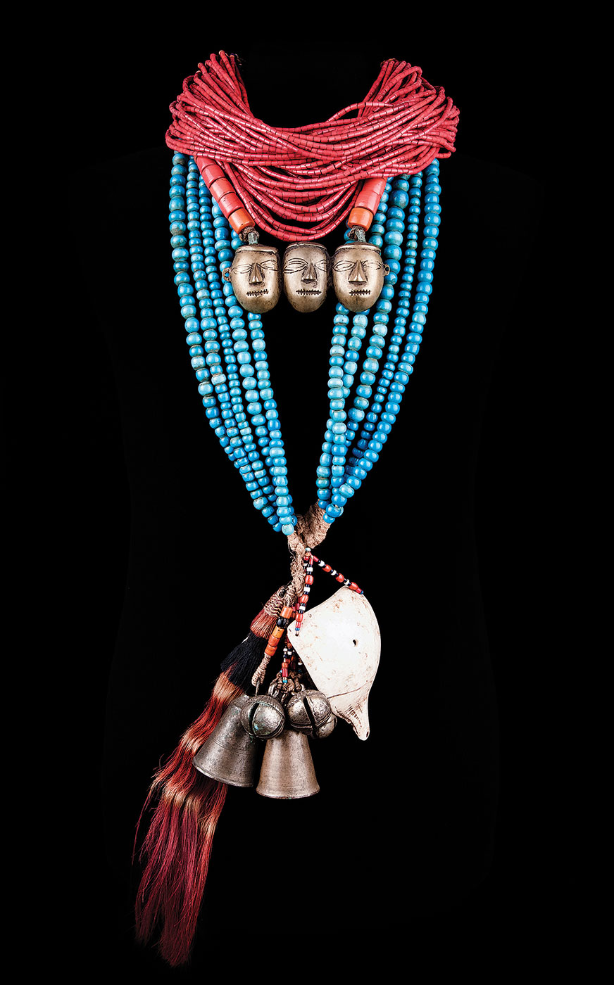 HEADHUNTER'S NECKLACES, Konyak Naga peoples, Nagaland, northeast India, of brass, glass beads, goat hair, conch shell, brass heads: 29.0 x 11.5 centimeters; blue beads: 58.0 centimeters; red beads: 26.5 centimeters, pre-1940.  Harry and Tiala M. Neufeld Collection.