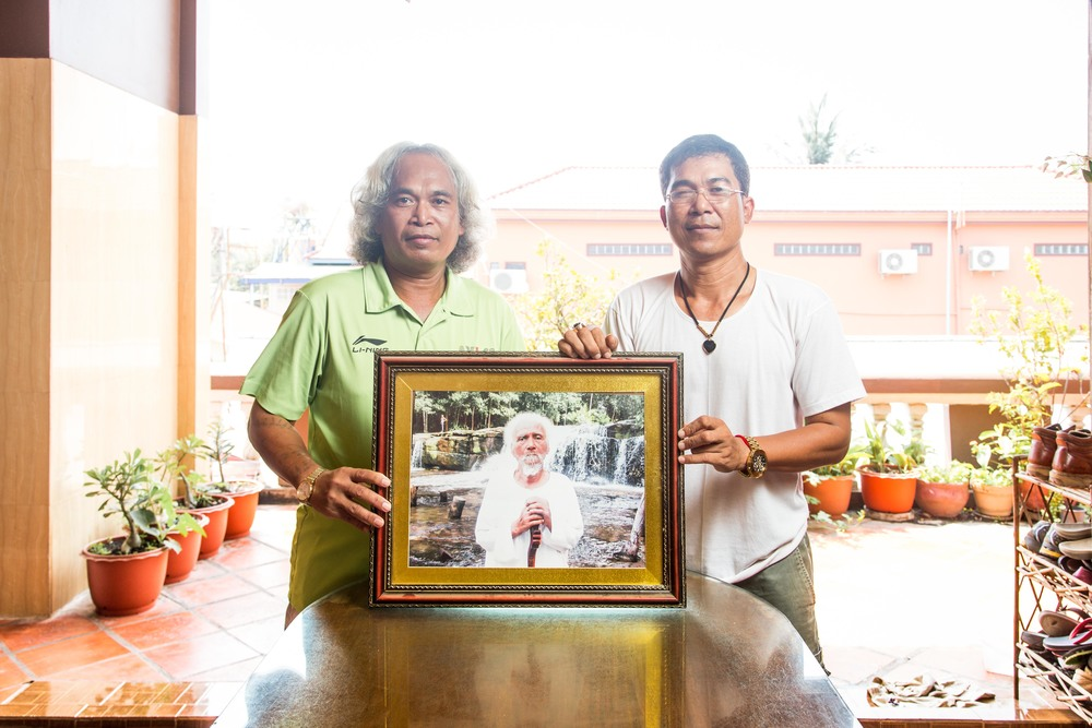 Sedtha (left) and Vudthy (right), pose with a photograph of their late father, Nhiem, who passed away in 2012.