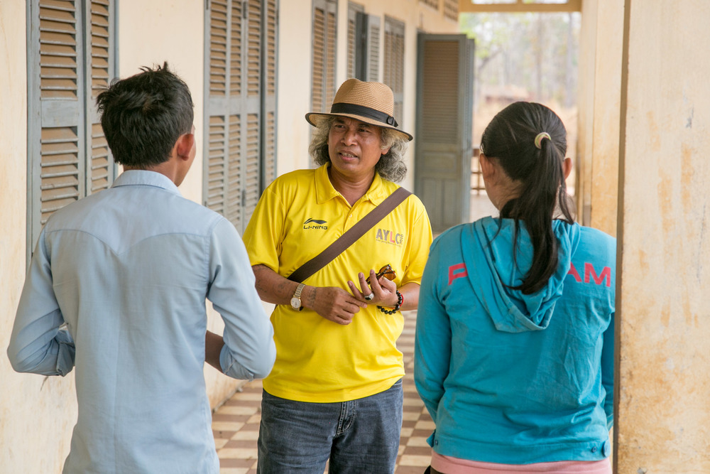 Sedtha speaking with a principal and teacher at a school that BFT supports in rural Siem Reap.