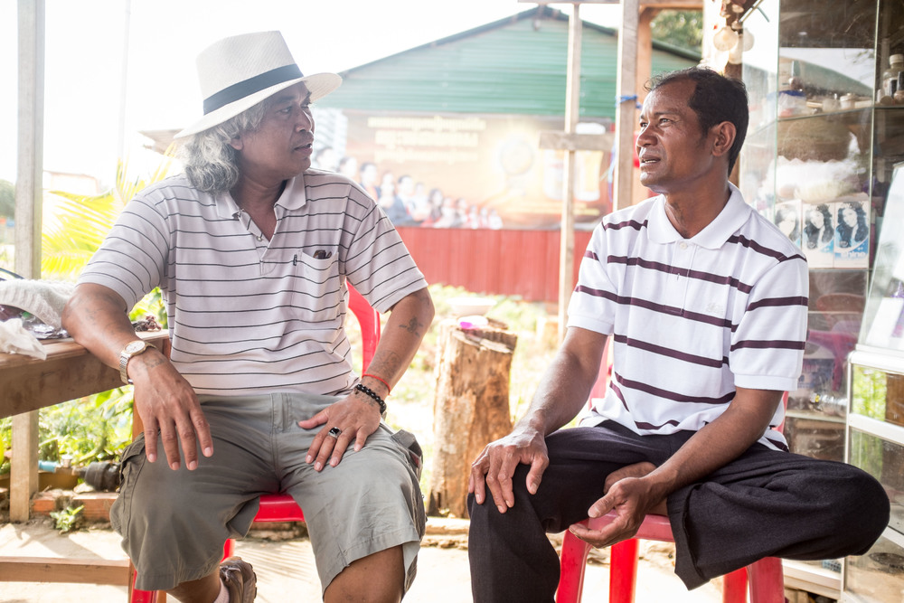 Sedtha speaking with a former Khmer Rouge soldier who lost his foot to a landmine. Sedtha has learned over the last forty years to let go of his hatred and forgive even those who helped perpetuate the genocide. At the end of this conversation, Sedtha would give the man school supplies so that his children could better pursue their educations.