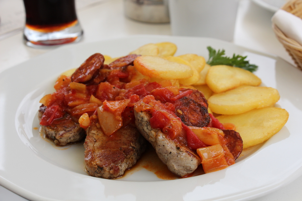 Grilled meat covered in tomato and onion sauce with slices of sausages