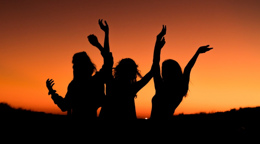 women in sunset celebrating.jpg
