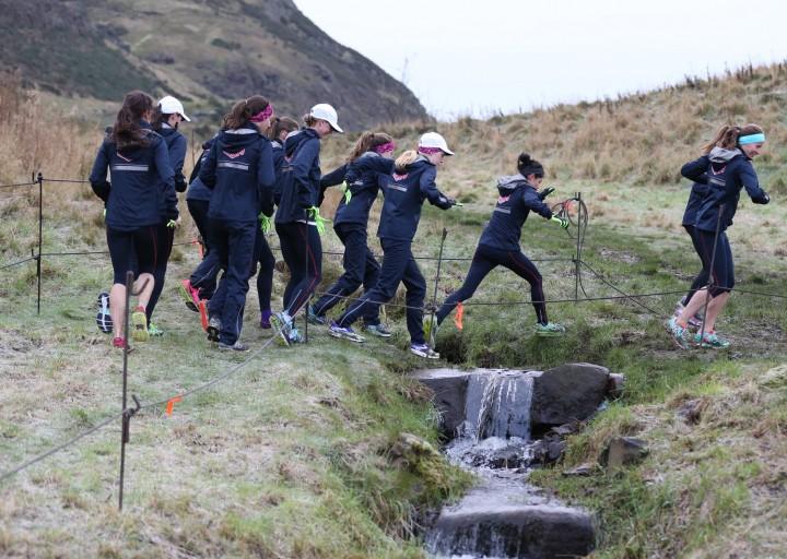 Senior women's team navigating the stream crossing during our pre-meet run