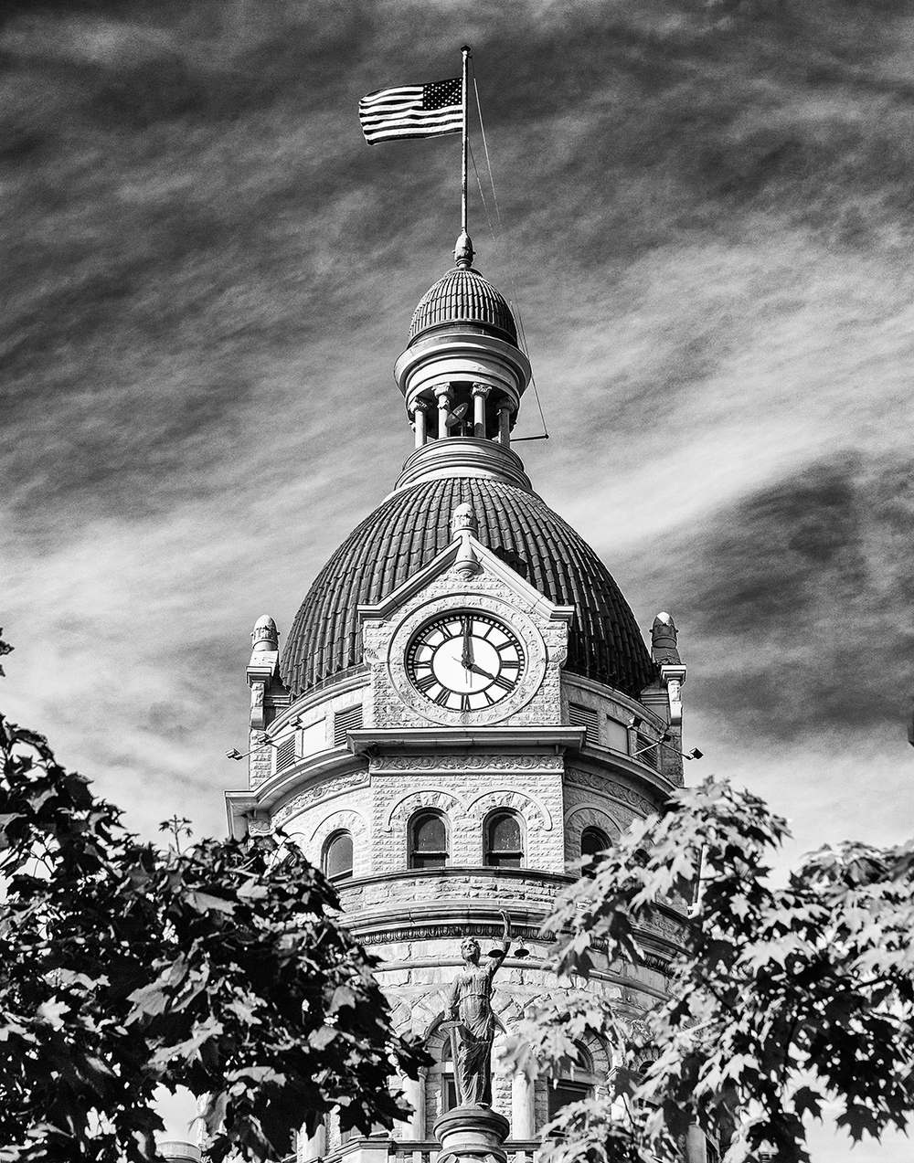This is the Trumbull County Courthouse located in Ohio.  I made this photograph in September 2015 after we attended a wedding at the gazebo outside of the courthouse.  This caught my eye with the way the trees framed the statue and when I pushed the shutter I already was thinking of making this into a B&W photograph.
