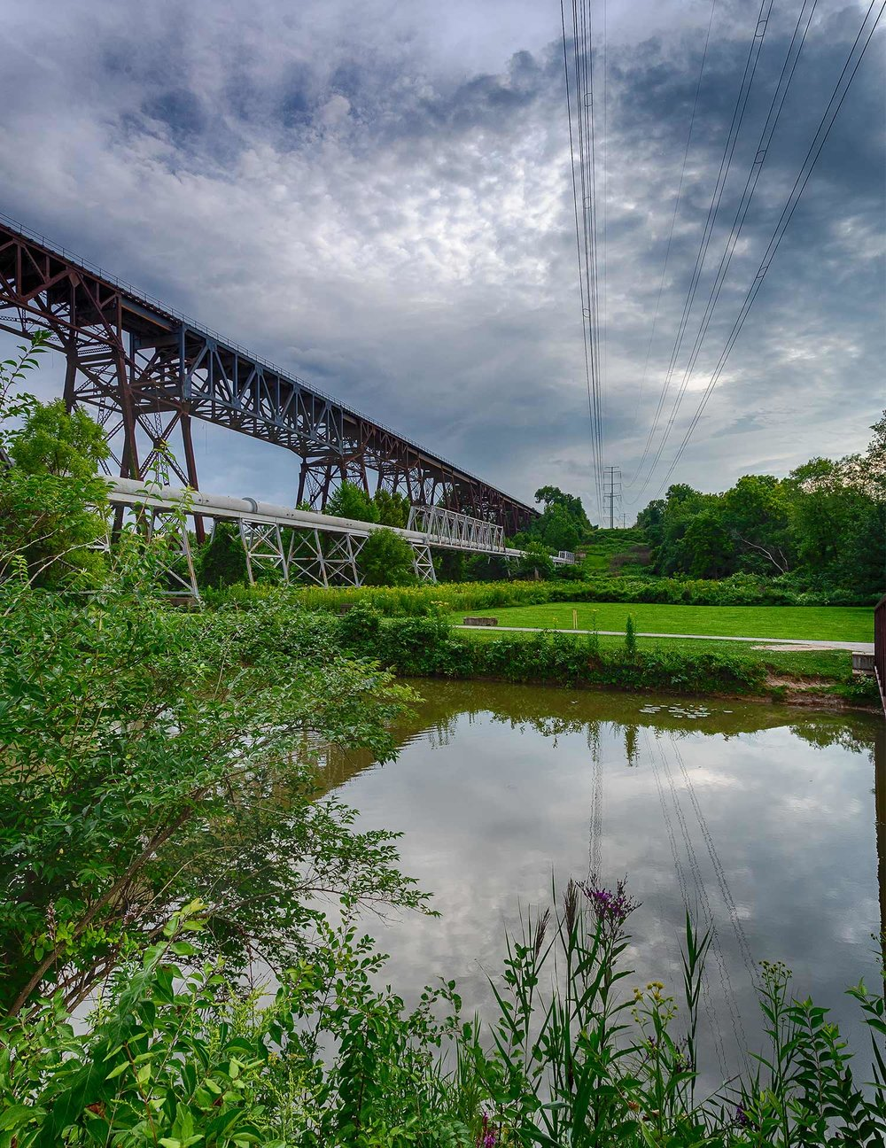 Ohio & Erie Canal Reservation.  The foreground is the Ohio & Erie Canal, on the right is a double circuited transmission line, the pipe on the left is an interceptor pipeline for sewage and on the far is a very active rail road bridge.