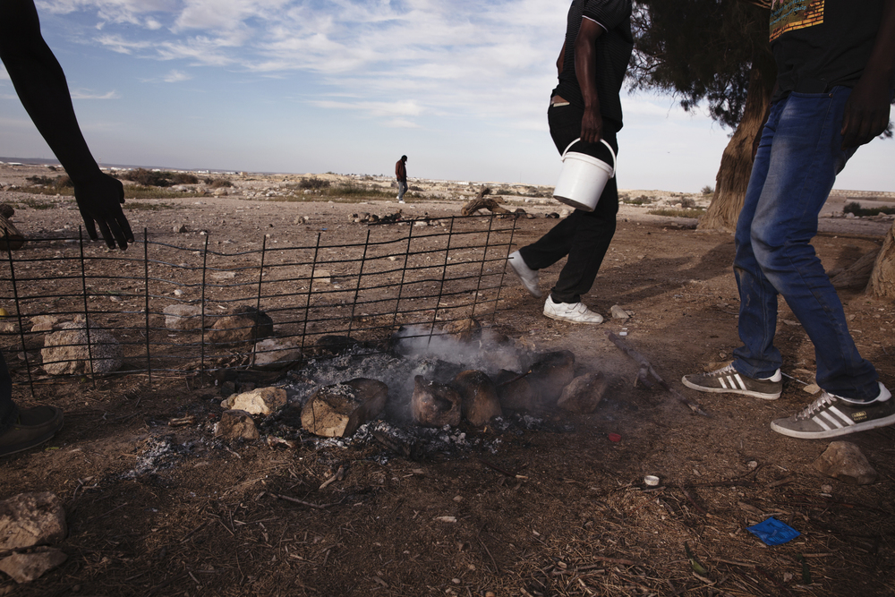 A group of detainees finishing up a barbeque in the desert. Many don't feel like they are being feed well in Holot, so detainees form groups and put their money together in a pot that they use to buy their own food.