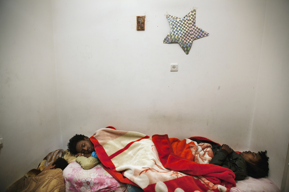 Eritrean asylum-seekers sleeping after working 12-hour shifts working in the hotel and restaurant industry. Many Africans live together to cope with the high rents in Tel Aviv.