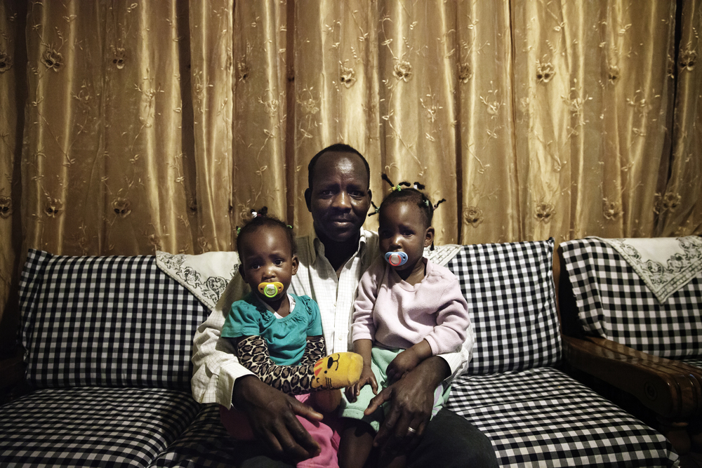 "Boshora Adam with his twin daughters in their home in Tel Aviv.  ""The hardest part about raising my children in Israel is that it's becoming more segregated. On the playground you notice that parents keep their children away from African children, and this worries me for my children's future."""