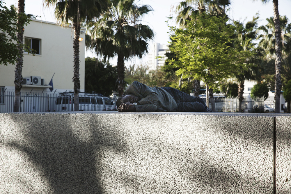 A man sleeping in Levinsky Park next to the Central bus station. When refugees are released into Israeli society they are given a bus ticket to this bus station in Tel Aviv, and it has become a central point for the African community.