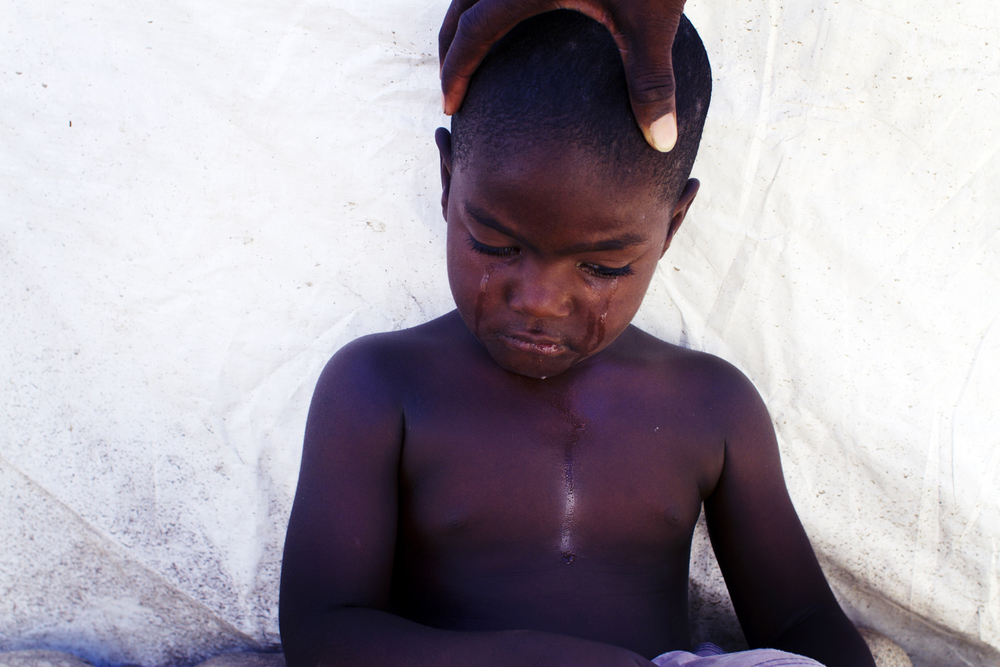 A upset boy living in the camp of Tet Ansanm in Port-au-Prince, Haiti. 2012.