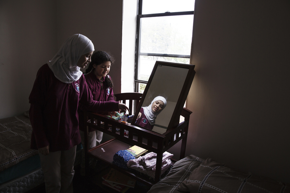 Sisters Nabiha Darbi, 13 and Hajar Darbi, 12 (curly hair) standing in their bedroom in their new home in New Jersey. They are Syrian refugees that recently resettled to America from a refugee camp in Jordan. For the New York Times.