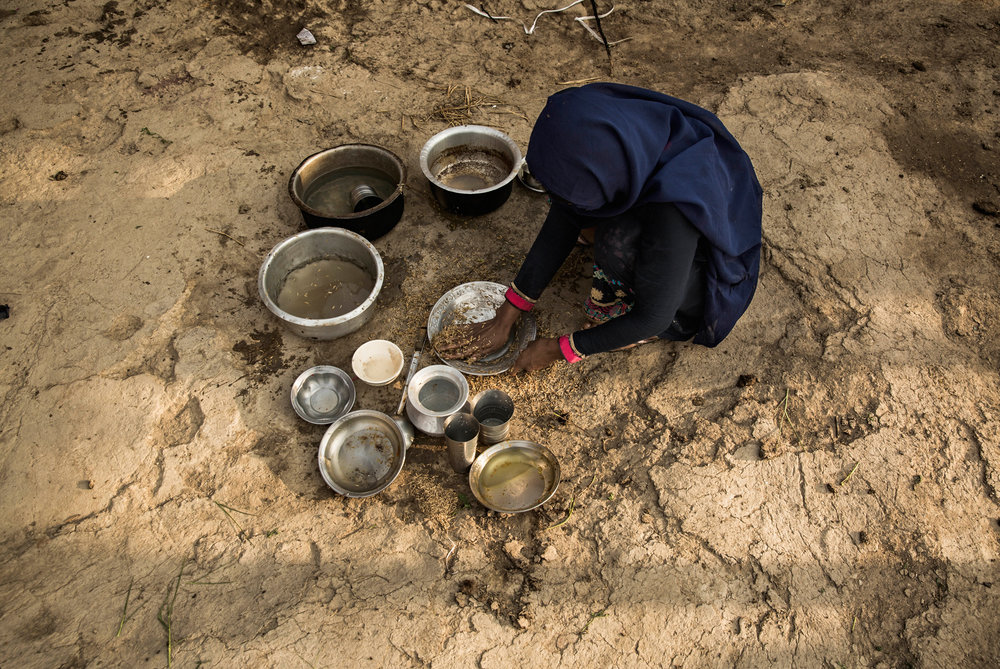 A woman in the water-poor village of Noor Muhammad Thaheem uses sand to wipe her dishes.