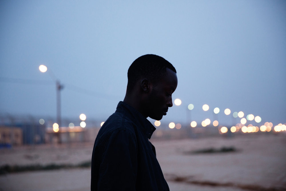 """MUTASIM ALI, a 28-year old asylum seeker from Sudan, stands outside Holot. He appealed the official """"invitation"""" to the detention center but was confined there for just over a year until his release this summer."""