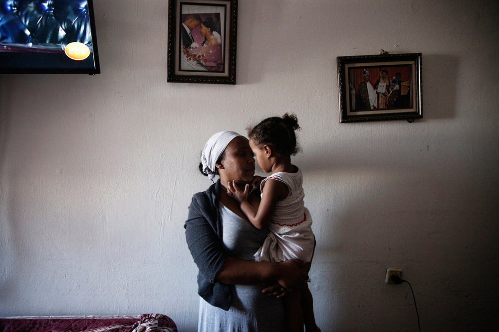 "YORDANOS YEMANE and her 3-year-old daughter, who was stabbed in the head by an Israeli man outside the central bus station in Tel Aviv last year. The perpetrator told the police that he had attacked ""a black baby"" because she was a ""black terrorist."" The perpetrator was found mentally unstable and unfit to stand trial."