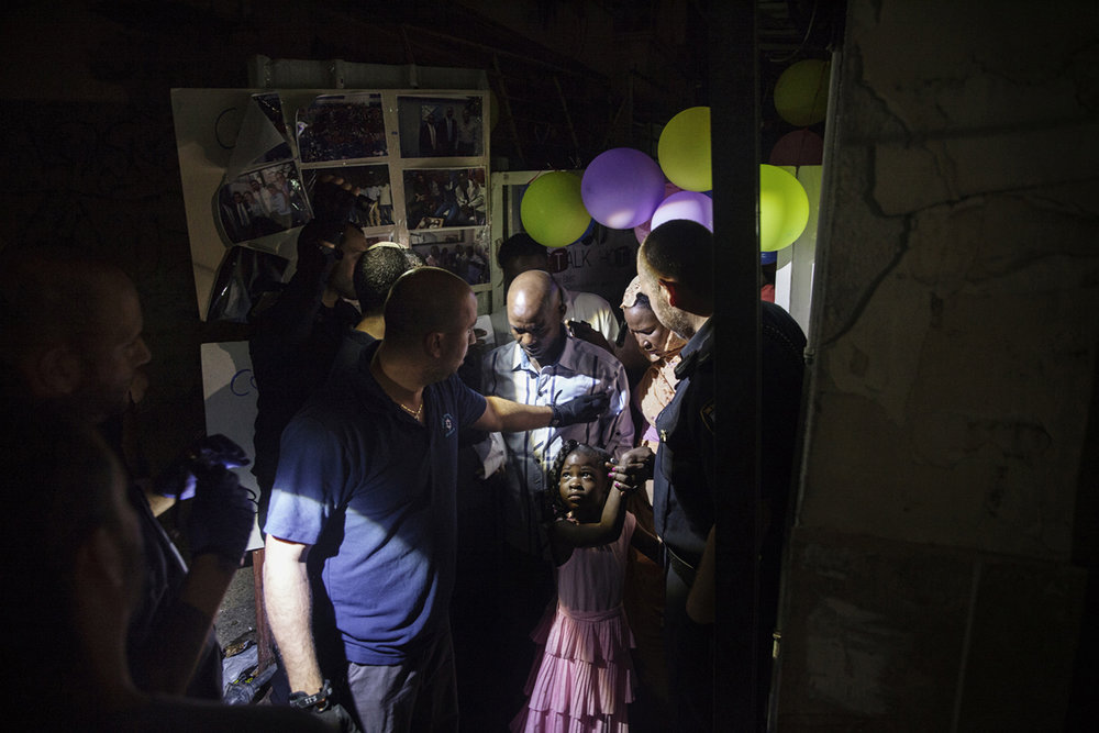 A little girl watched as Israeli immigration police officers raided a graduation party for a Sudanese asylum seeker in Tel Aviv.