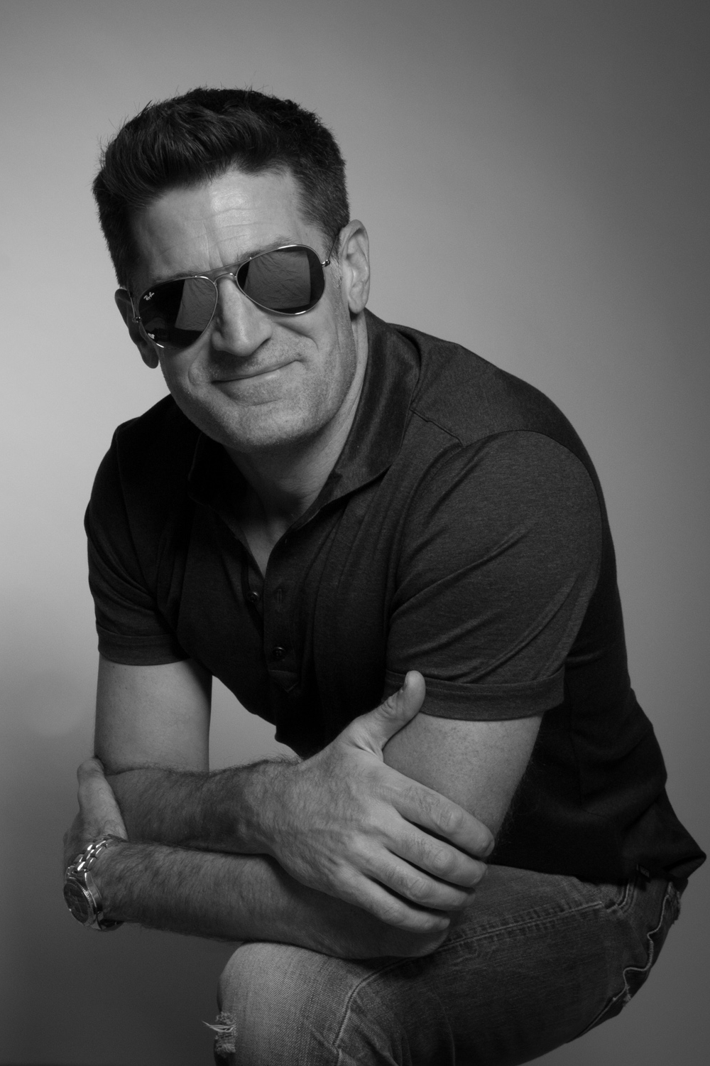 black and white portrait of a fun loving entrepreneur in aviator glasses