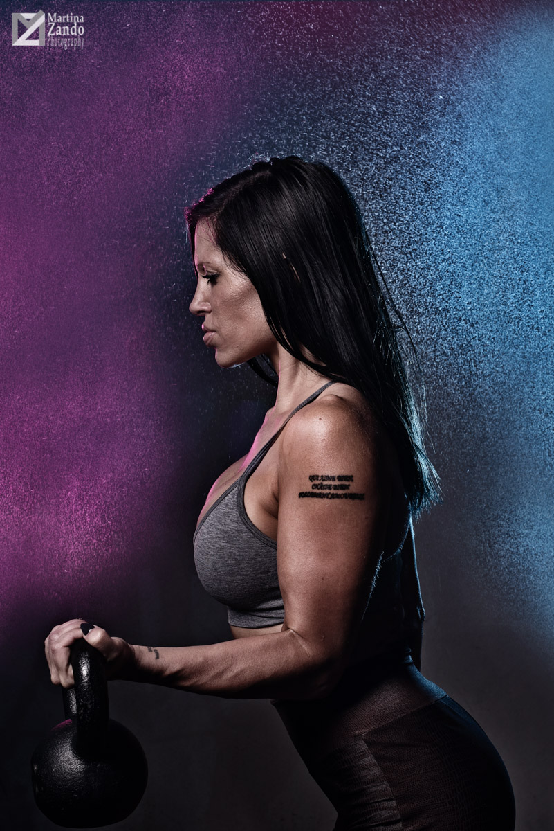 purple and blue mist lifestyle portrait of athlete with kettle bell