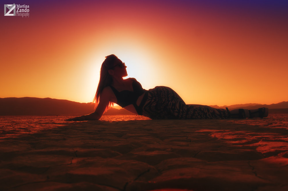curves of woman in the desert at sunset