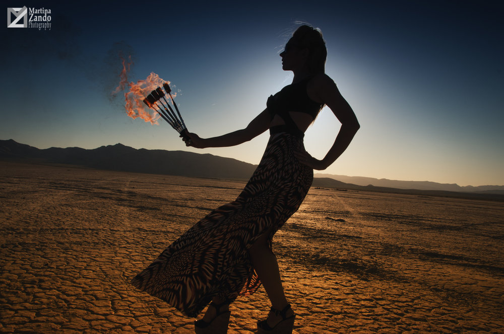 woman holding fire in the desert