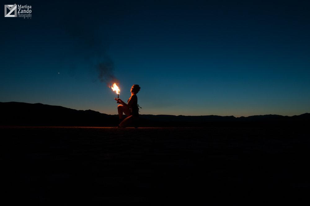 woman lit by fire in desert photoshoot