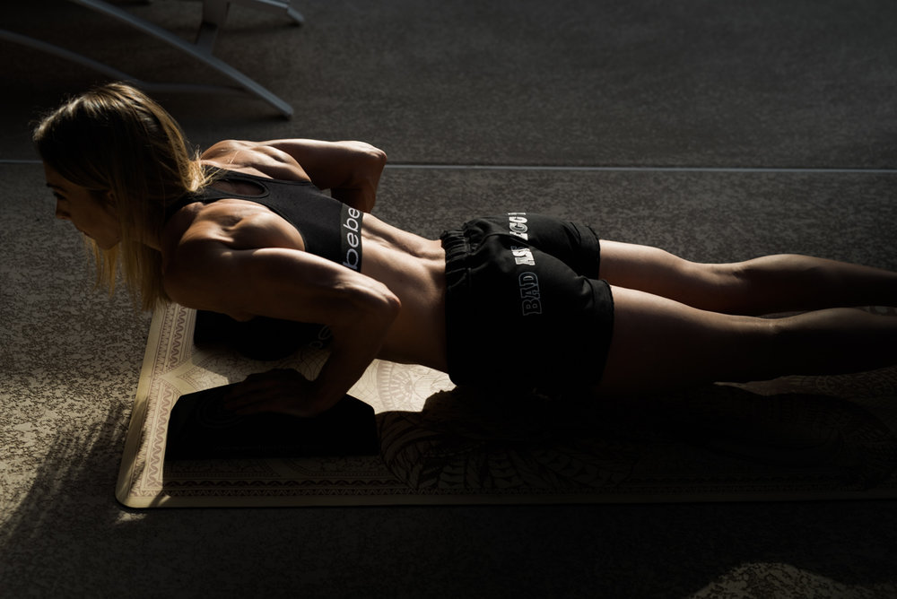 fitness model doing a push up in sunset light