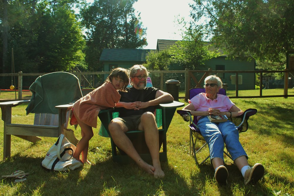 My niece Emma, Me, and Mom with a book in her lap at her favorite place—the Keene Valley pool—with grand kids and everyone a friend and welcomed sight.